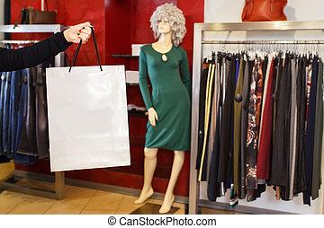 hand holding white shopping bag