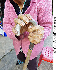 closeup hand of an old asian female pensioner on a walking stick or a cane.