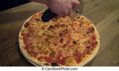 Closeup hand of chef baker cutting pizza