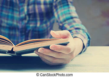 Closeup hand open book for reading concept background. Toned...