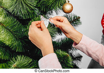 Closeup, hands decorate the Christmas tree, on a white background.