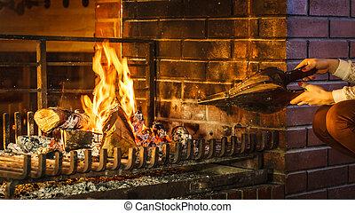 Closeup hands fireplace making fire with bellows. - Closeup...