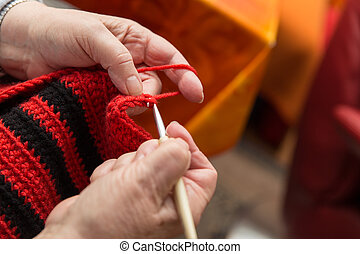 closeup hands from a senior woman with a crochet hook and wool