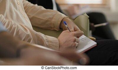 Closeup hands of adult woman noting at seminar - Closeup...