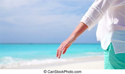 Closeup hands of couple background the sea. Young couple on white beach. SLOW MOTION VIDEO.