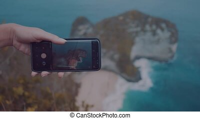 Closeup hands with mobile phone doing photo of Kelingking Beach cliffs in Nusa Penida, Bali