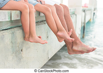 Closeup hanging their legs into the water on wooden pier