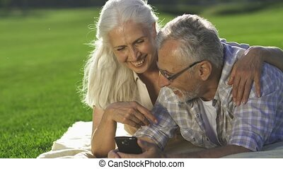 Closeup happy seniors enjoying modern device
