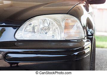 Closeup headlight of black coupe