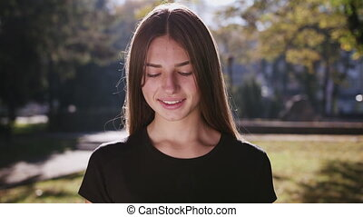Closeup headshot of confident smiling happy pretty young woman, isolated background of blurred trees. Positive human emotion facial expression feelings, attitude, perception