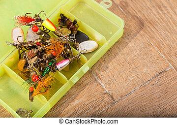 closeup heaps of fishing bait lures in box