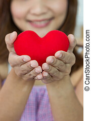 Closeup heart shape with women's hands in vertical