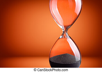 Closeup hourglass on orange background