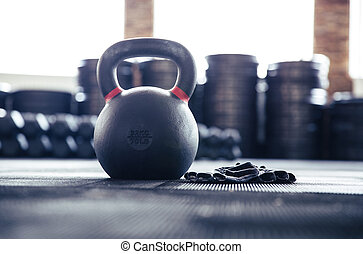 Closeup image of a kettle ball and sports gloves in gym