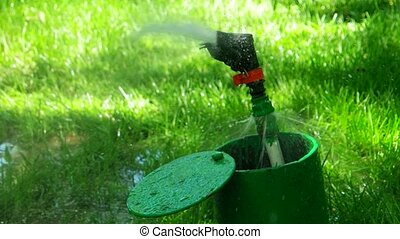 Closeup image of a sprinkler on a sunny summer day during watering the green lawn in garden.