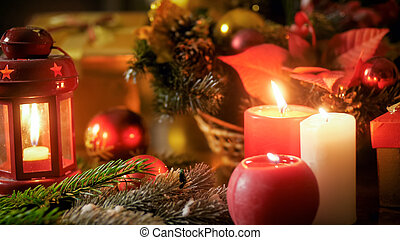 Closeup image of burning candles and Christmas decorations on wooden table. Perfect backgorund for winter holidays and celebrations