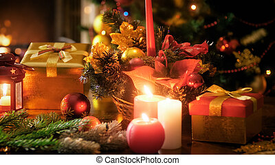 Closeup image of burning candles on wooden table in living room decorated for Christmas