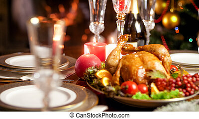 Closeup image of candles burning on served hristmas dinner table with baked chicken