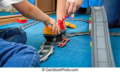 Closeup image of caring parent playing with child on floor at playroom
