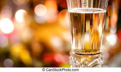 Closeup image of champagne filled glass against glowing colorful Christmas lights