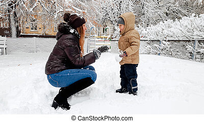 Closeup image of cheerful smiling young mother in broun coat and hat with her pretty son in beige jacket have fun to playing the snow balls with snow on the Playground in the Park