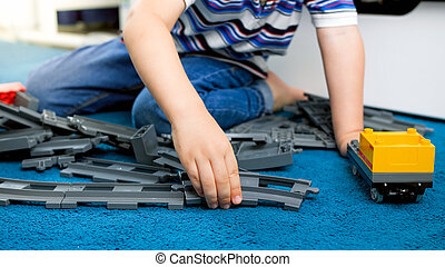Closeup image of child's hand assembling toy railroad on floor