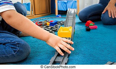 Closeup image of child's hand palying with toy train and railroad on floor