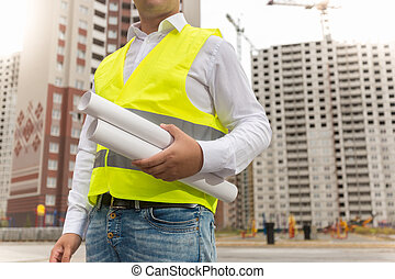 Closeup image of construction engineer holding blueprints