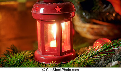 Closeup image of decorative lantern with burning candle on Christmas tree branch