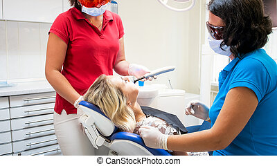 Closeup image of dentist curing patients teeth with UV light lamp
