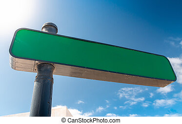Closeup image of empty blank directional sign on street against clear blue sky and sun. Copy space. Place for your text