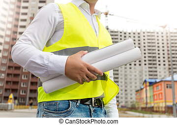 Closeup image of engineer in safety vest holding rolled blueprints