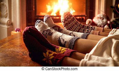 Closeup image of family feet wearing woolen socks warming on cold night at fireplace