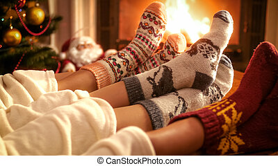 Closeup image of family warming by the fireplace on Christmas eve
