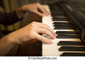 Closeup image of female hands playing on piano
