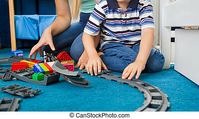 Closeup image of little toddler boy wth young mother assembling toy railroad on floor