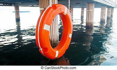 Closeup image of orange lifesaving buoy hanging on long...