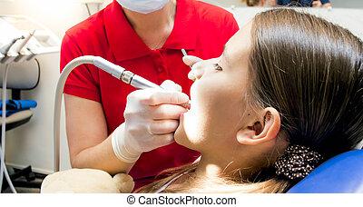 Closeup image of pediatric dentist using dental drill during girrls teeth treatment