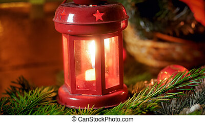 Closeup image of red decorative lantern with burning candle on fire tree branch. Perfect backgorund for winter holidays and celebrations