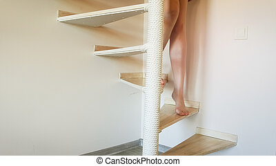 Closeup image of sexy bearefoot woman with long legs walking down the stairs
