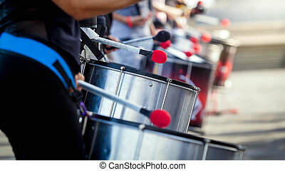 Closeup image of street musical band of drummers playing on street