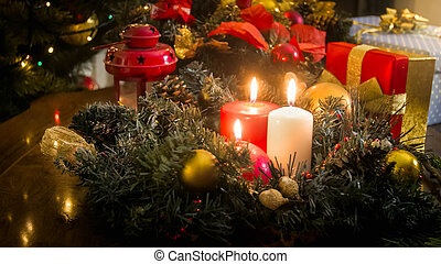 CLoseup image of three burning candles on wooden table decorated for Christmas celebration