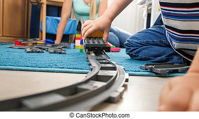 Closeup image of toy railroad with colorful train on floor at child's room