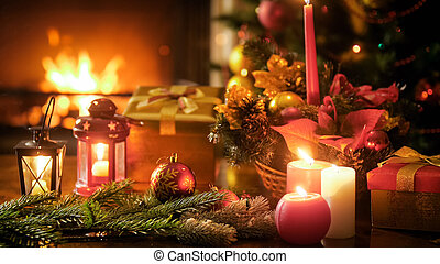 Closeup image of traditional Christmas decorations and candles on wooden table against fireplace