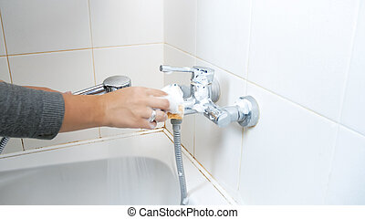 Closeup image of young woman cleaning water faucet in bathroom with detergent
