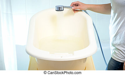 Closeup image of young woman filling baby small bathtub in bathroom