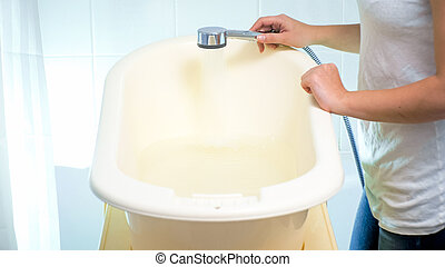 Closeup image of young woman filling bathtub with water for her baby