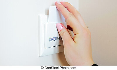 Closeup image of young woman in hotel room inserting key card in holder