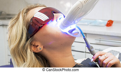 Closeup image of young woman in protective glasses sitting in dentist chair during teeth whitening procedure