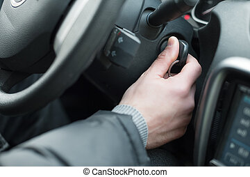 Closeup inside vehicle of hand holding key in ignition, start engine key